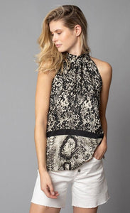 Front, top half view of a woman with her left hand in the left pocket of her white shorts. On the top, the woman is wearing the lola & sophie border animal print halter top. This sleeveless top has a high halter neck and a mix of two different snake skin prints separated by a black border that runs horizontally across the waist.