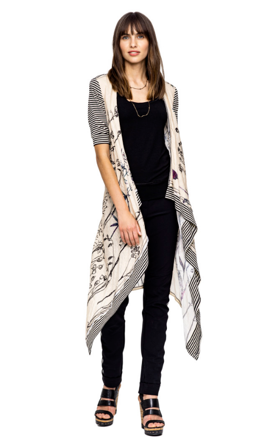 Front full body view of a woman wearing black pants, a black tank, and the Beate Heymann Linen Wrap/Cardi. This wrap is cream colored with floral print. The sleeves and hem are black and white striped.