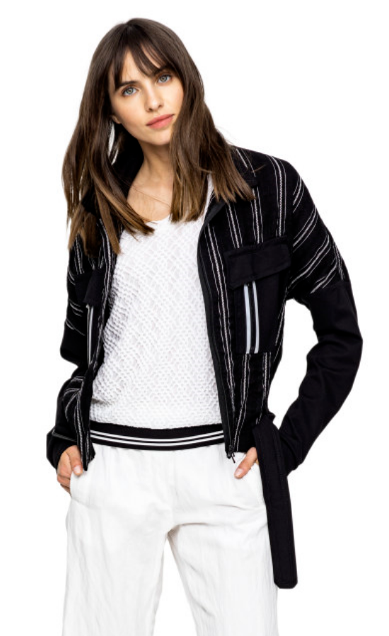 Front, top half view of a woman wearing white pants a white top and the Beate Heymann Stripped Jacket. This jacket is black with white stripes. The sleeves are solid black and the front has two patch, solid black pockets with a single white stripe on them. The jacket has a zip up front and belt near the bottom.