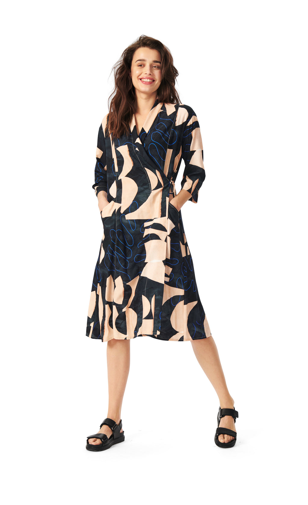 Front full body view of a woman wearing the bitte kai rand monstera wrap dress. This dress is nude with black and blue abstract print on it. The dress has a left side tie that creates a layered over look. The sleeves are 3/4 length and the dress ends at the knees.