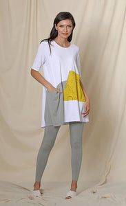 Front full body view of a woman wearing the chalet fallon tunic. This tunic is white with a yellow patch and a grey patch pocket in the front. This tunic sits below the hips.
