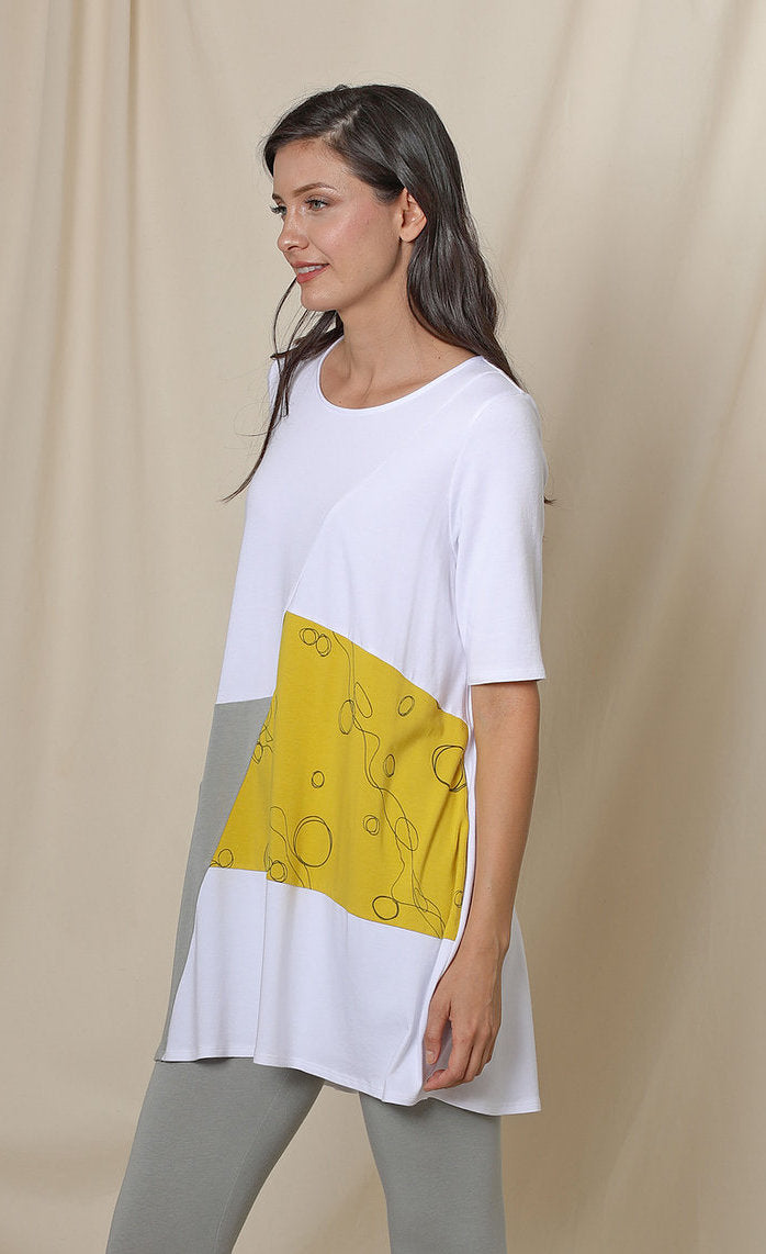 Front left sided top half view of a woman wearing the chalet fallon tunic. This tunic is white with a yellow patch and a grey patch pocket in the front. This tunic sits below the hips.
