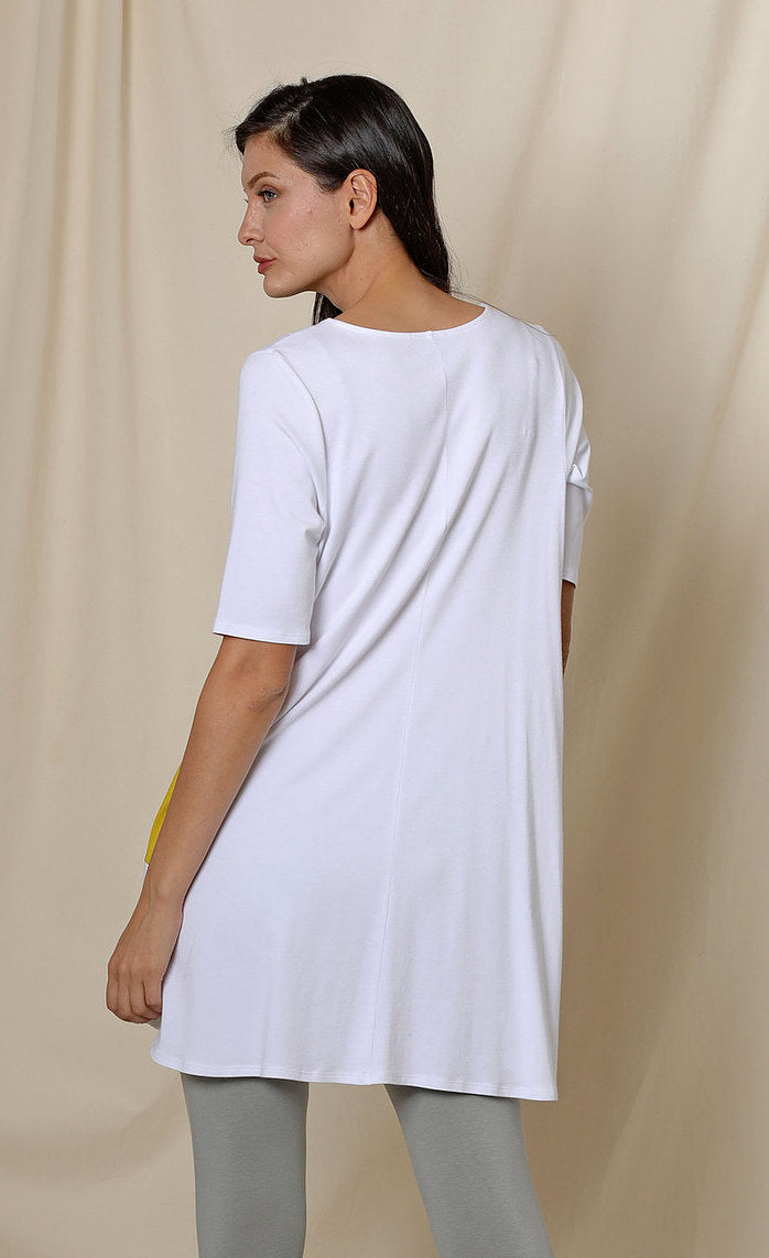 Back top half view of a woman wearing the chalet fallon tunic. This tunic is white and sits below the hips.