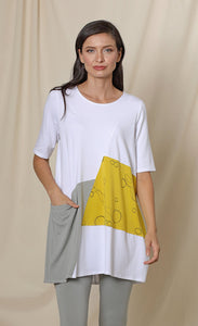 Front top half view of a woman wearing the chalet fallon tunic. This tunic is white with a yellow patch and a grey patch pocket in the front. This tunic sits below the hips.