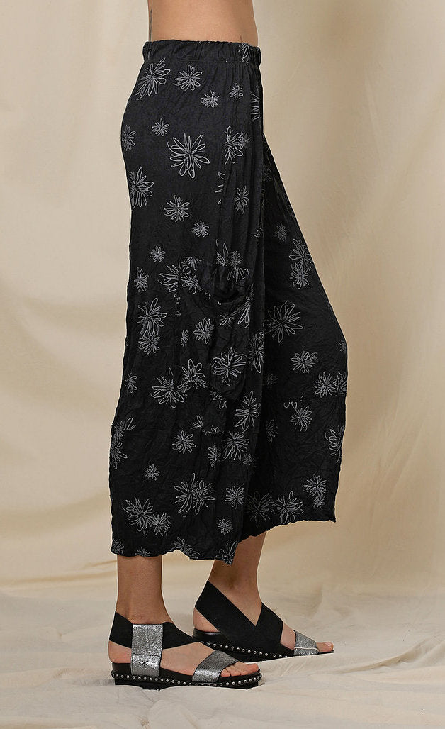 Right side, bottom half view of a woman wearing the chalet hallie pant. This pant is black with white flowers. It has a crinkled look and two draped side pockets. The pants end above the ankles.