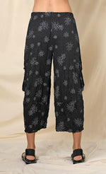 Load image into Gallery viewer, Back bottom half view of a woman wearing the chalet hallie pant. This pant is black with white flowers. It has a crinkled look and two draped side pockets. The pants end above the ankles.