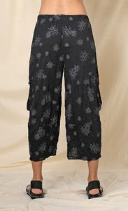 Back bottom half view of a woman wearing the chalet hallie pant. This pant is black with white flowers. It has a crinkled look and two draped side pockets. The pants end above the ankles.