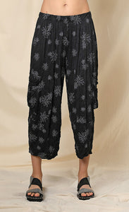 Front bottom half view of a woman wearing the chalet hallie pant. This pant is black with white flowers. It has a crinkled look and two draped side pockets. The pants end above the ankles.
