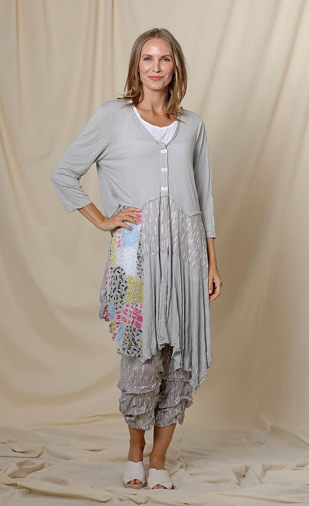 Front full body view of a woman wearing the chalet orla jacket. The jacket in this image is grey with a patchwork print on the right side, a 3 button front, 3/4 length sleeves, and an asymmetrical hem.