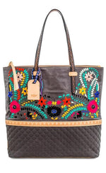 Load image into Gallery viewer, Front view of the consuela silverlake market tote. This tote is grey with a quilted like bottom and light tan trim. The straps are thin. On the front of the tote is blue pink and orange floral embroidery.