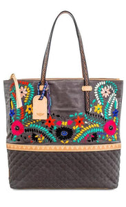 Front view of the consuela silverlake market tote. This tote is grey with a quilted like bottom and light tan trim. The straps are thin. On the front of the tote is blue pink and orange floral embroidery.