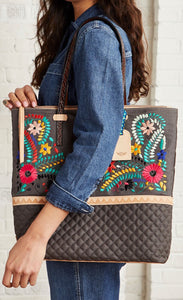 Front view of a model carrying the consuela silverlake market tote on her shoulder. This tote is grey with a quilted like bottom and light tan trim. The straps are thin. On the front of the tote is blue pink and orange floral embroidery.