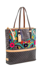 Load image into Gallery viewer, Front right side view of the consuela silverlake market tote. This tote is grey with a quilted like bottom and light tan trim. The straps are thin. On the front of the tote is blue pink and orange floral embroidery.