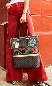 Front view of a model in red pants leaning on a red building and carrying the consuela silverlake market tote. This tote is grey with a quilted like bottom and light tan trim. The straps are thin. On the front of the tote is blue pink and orange floral embroidery.