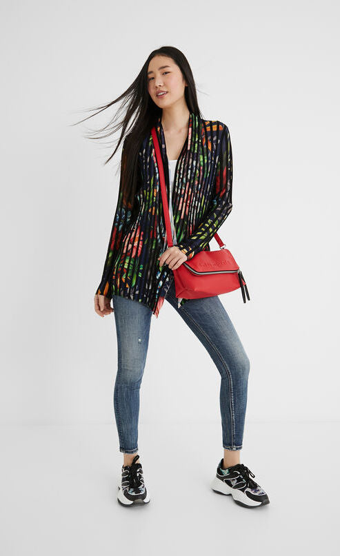 Front full body view of a woman wearing skinny jeans, tennis shoes, and the Desigual namur pleated flower jacket. This long-sleeved, open front jacket is black with floral print all over it. The jacket has black pleats running vertically in a striped fashion.