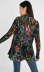 Load image into Gallery viewer, Back top half view of a woman wearing skinny jeans and the Desigual namur pleated flower jacket. This long-sleeved jacket is black with floral print all over it. The jacket has black pleats running vertically in a striped fashion.