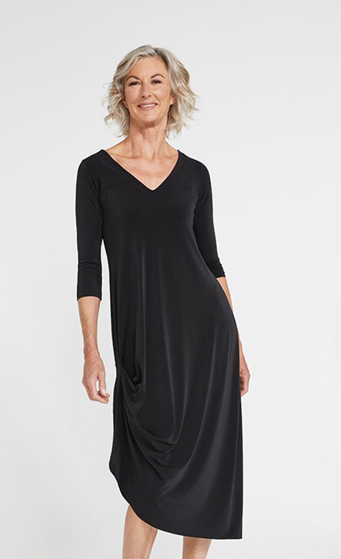 Front angle of woman wearing a black mid-length drama dress with 3/4 sleeves from Sympli