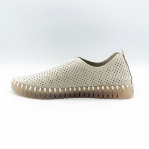 Inner side view of the Ilse Jacobsen flat shoe in creme. This shoe has a gummy sole. The upper features perforated holes and sparkles