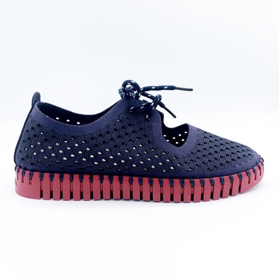 Outer side view of the ilse jacobsen tie flat. This flat is navy with a red sole. The upper has a scale like pattern with perforated tiny holes all over it. The shoe has a lace up front.