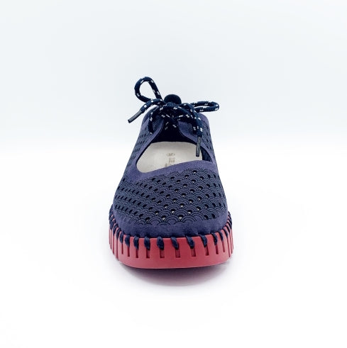 Front view of the ilse jacobsen tie flat. This flat is navy with a red sole. The upper has a scale like pattern with perforated tiny holes all over it. The shoe has a lace up front.