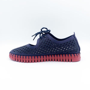 Inner side view of the ilse jacobsen tie flat. This flat is navy with a red sole. The upper has a scale like pattern with perforated tiny holes all over it. The shoe has a lace up front.