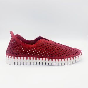 Outer view of the ilse jacobsen tulip flat in deep red. This flat shoe has a white sole and a scale-like red upper. The upper is perforated with tiny holes all over it.