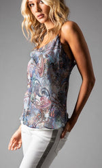 Load image into Gallery viewer, Side top half view of a woman wearing the Cowl Neck Cami from Lola & Sophie. This cami has thin straps and a soft paisley print that is primarily blue with mixes of red and other colors.
