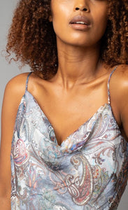 Zoomed in front view the neckline of a woman wearing the Cowl Neck Cami from Lola & Sophie. This cami has thin straps and a soft paisley print that is primarily blue with mixes of red and other colors.