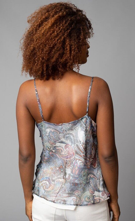 Back top half view of a woman wearing the Cowl Neck Cami from Lola & Sophie. This cami has thin straps and a soft paisley print that is primarily blue with mixes of red and other colors.