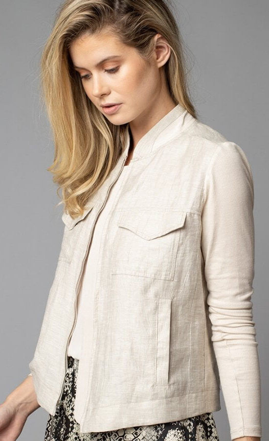 Front, top half left side view of a woman wearing the Lola & Sophie Crinkle Linen Jean Jacket. The sand colored jacket features two front, fold over breast pockets, a zipper front, a linen body, and fitted long sleeves.