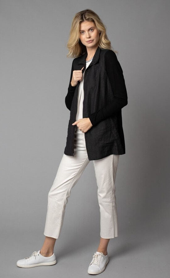 Front, left-sided full body view of a woman wearing white capris and the Lola & Sophie Crinkle Linen Zip-Front Long Black Jacket. This jacket has a flat collar, a zip up front, front pockets, and fitted long sleeves.