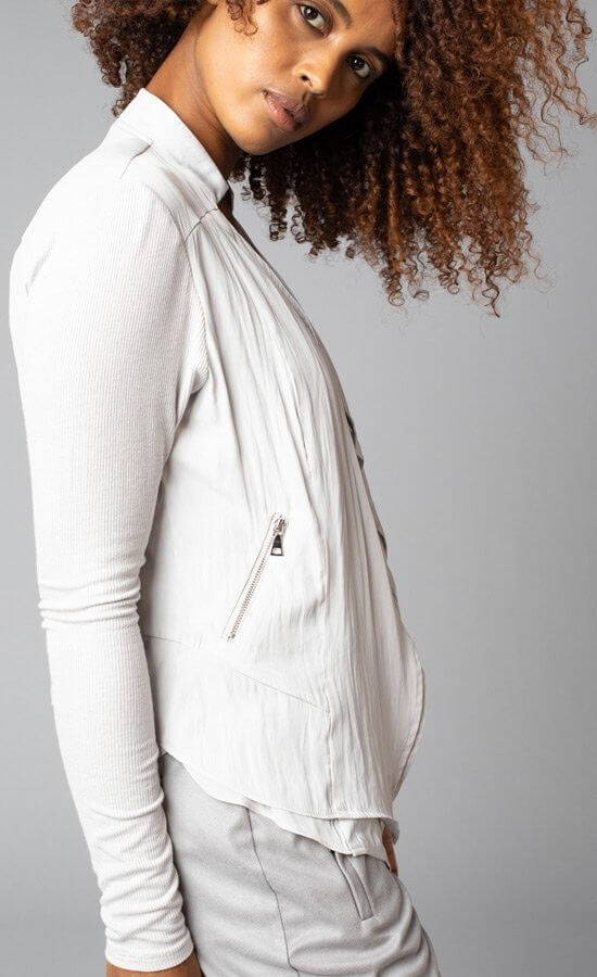 Side view of a woman wearing the no closure moto jacket from Lola & Sophie. This jacket is eggshell colored and thin with fitted sleeves and a flowy satin front that has front zipper pockets.