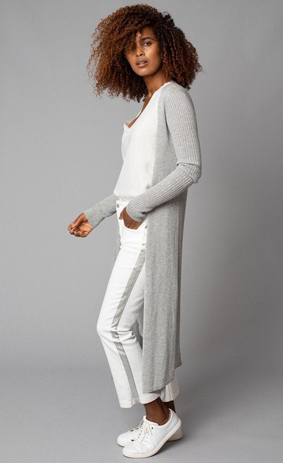 Left side, full body view of a woman with her hands in the pocket of her white pant with a grey side stipe. The woman is also wearing the lola & sophie white v-neck tank under the lola & sophie split back cardi. This cardigan is grey and goes down to the model's ankle. The long sleeves are fitted and ribbed.