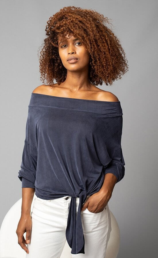 Front, top half view of a woman with her left hand in the pockets of her white jeans. On the top she is wearing the Lola & Sophie Off the Shoulder Top. This top is a greyish-midnight blue. The sleeves are rolled up to the elbows and the front has a left sided tie at the bottom.