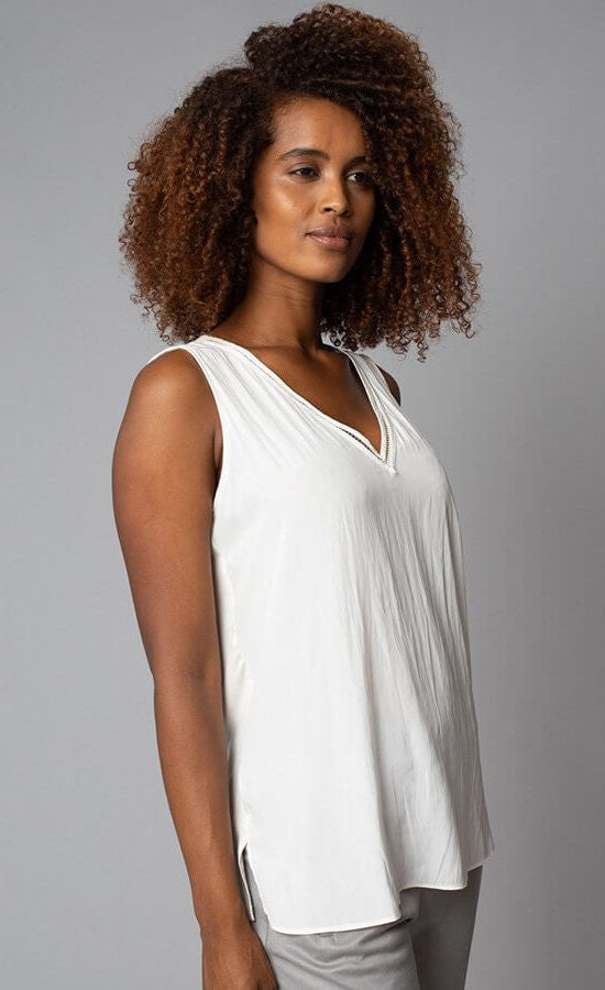 Front, right-sided view of the top half of a woman wearing the Lola & Sophie V-Neck tank. This tank is eggshell colored and has a small side slit near the bottom and detailed trim around the v-neck.