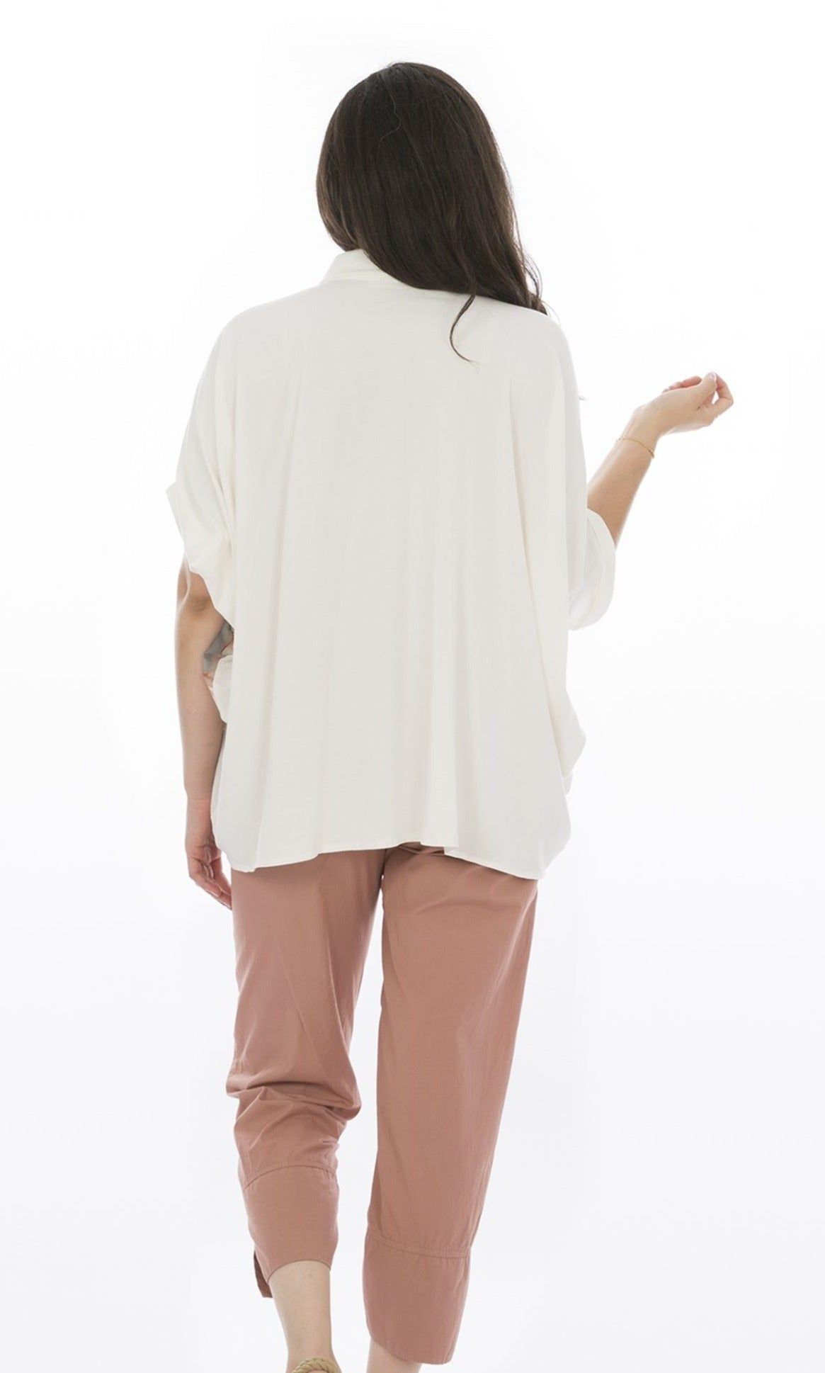 Back, top half view of a woman wearing pink capris and the Luukaa Watercolor Shirt. The back of this shirt is completely white and oversized. The sleeves are short and dolman-like.