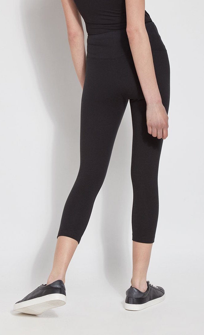 Back bottom half view of a woman wearing Lysse's Flattering Cotton Crop Legging. These leggings are black and have a high-rise, large waistband.