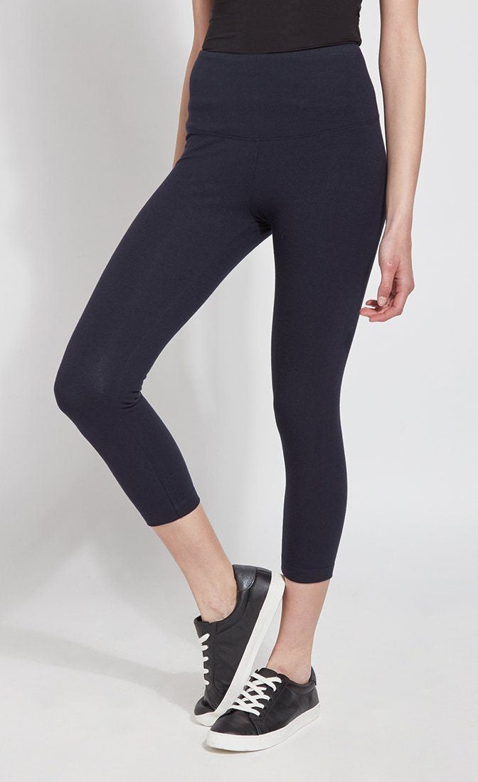 Front bottom half view of a woman wearing Lysse's Flattering Cotton Crop Legging. These leggings are navy and have a high-rise, large waistband.
