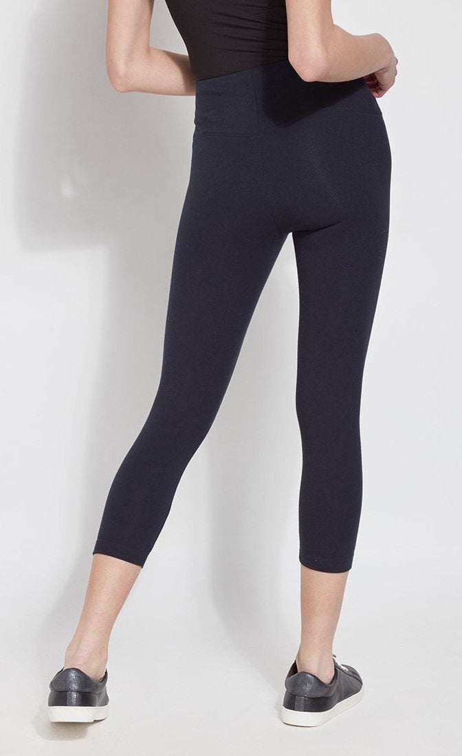 Back bottom half view of a woman wearing Lysse's Flattering Cotton Crop Legging. These leggings are navy and have a high-rise, large waistband.