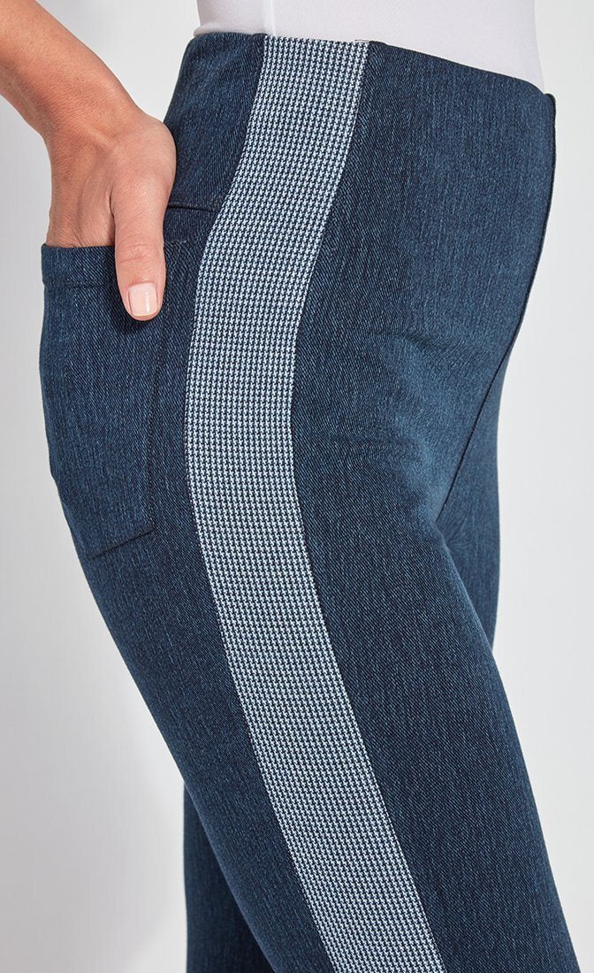 Right side, close up view of a woman wearing the Lysse Nomad Crop Leggings. These leggings are dark denim with a side blue and white houndstooth printed stripe going down the entire leg. The woman has her hands in the back pocket of the leggings.