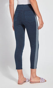 Back view of the bottom half of a woman wearing the Lysse Nomad Crop Leggings. These leggings are dark denim with a side blue and white houndstooth printed stripe going down the entire leg. The leggings have two large back pockets and cut off above the ankles. The woman is also wearing flat beige sandals.
