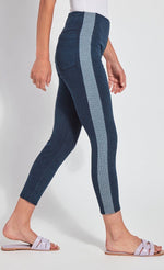 Load image into Gallery viewer, Right side view of the bottom half of a woman with one leg in front of the other and wearing the Lysse Nomad Crop Leggings. These leggings are dark denim with a side blue and white houndstooth printed stripe going down the entire leg. The leggings cut off above the ankles and the woman is wearing flat beige sandals.