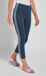 Front, right side view of the bottom half of a woman wearing the Lysse Nomad Crop Leggings. These leggings are dark denim with a side blue and white houndstooth printed stripe going down the entire leg. The leggings cut off above the ankles and the woman is wearing flat beige sandals.