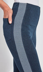 Load image into Gallery viewer, Right side, close up view of a woman wearing the Lysse Nomad Crop Leggings. These leggings are dark denim with a side blue and white houndstooth printed stripe going down the entire leg. The woman has her hands in the back pocket of the leggings.