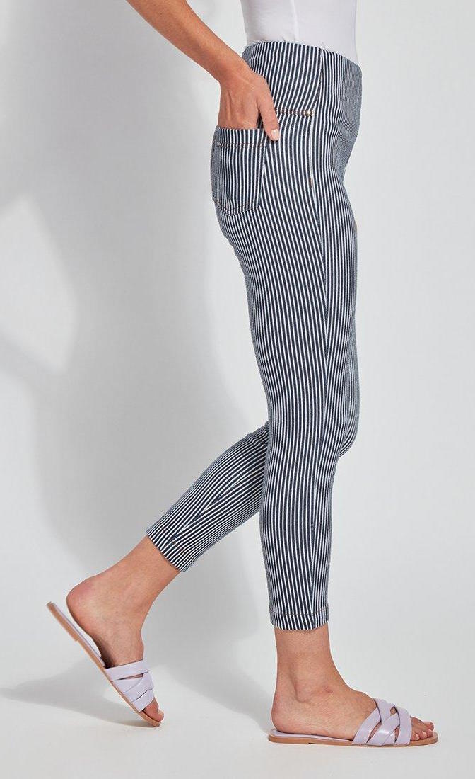 Right side bottom half view of a woman wearing the Lysse Toothpick Crop Pattern Legging with her hand in the back right pocket. These leggings are indigo and white pinstriped and high waisted and have two back pockets.