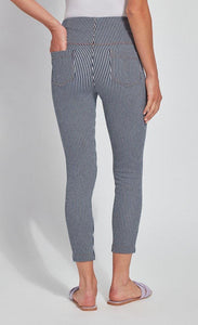Back bottom half view of a woman wearing the Lysse Toothpick Crop Pattern Legging with her hand in the back left pocket. These leggings are indigo and white pinstriped and high waisted and have two back pockets.