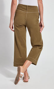 Back bottom half view of a woman wearing the lysse jade wide leg crop denim pant. This pant is khaki colored. It has contrasting white stitching and a hem that sits above the ankles.