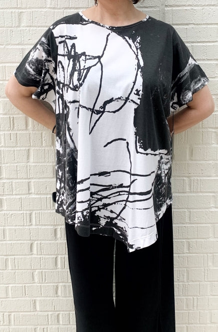 Front top half view of a woman wearing the moyuru short sleeve printed top. This top is white with black abstract print and an asymmetrical hem.