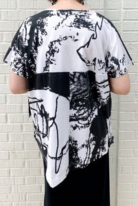 Back top half view of a woman wearing the moyuru short sleeve printed top. This top is white with black abstract print and an asymmetrical hem.
