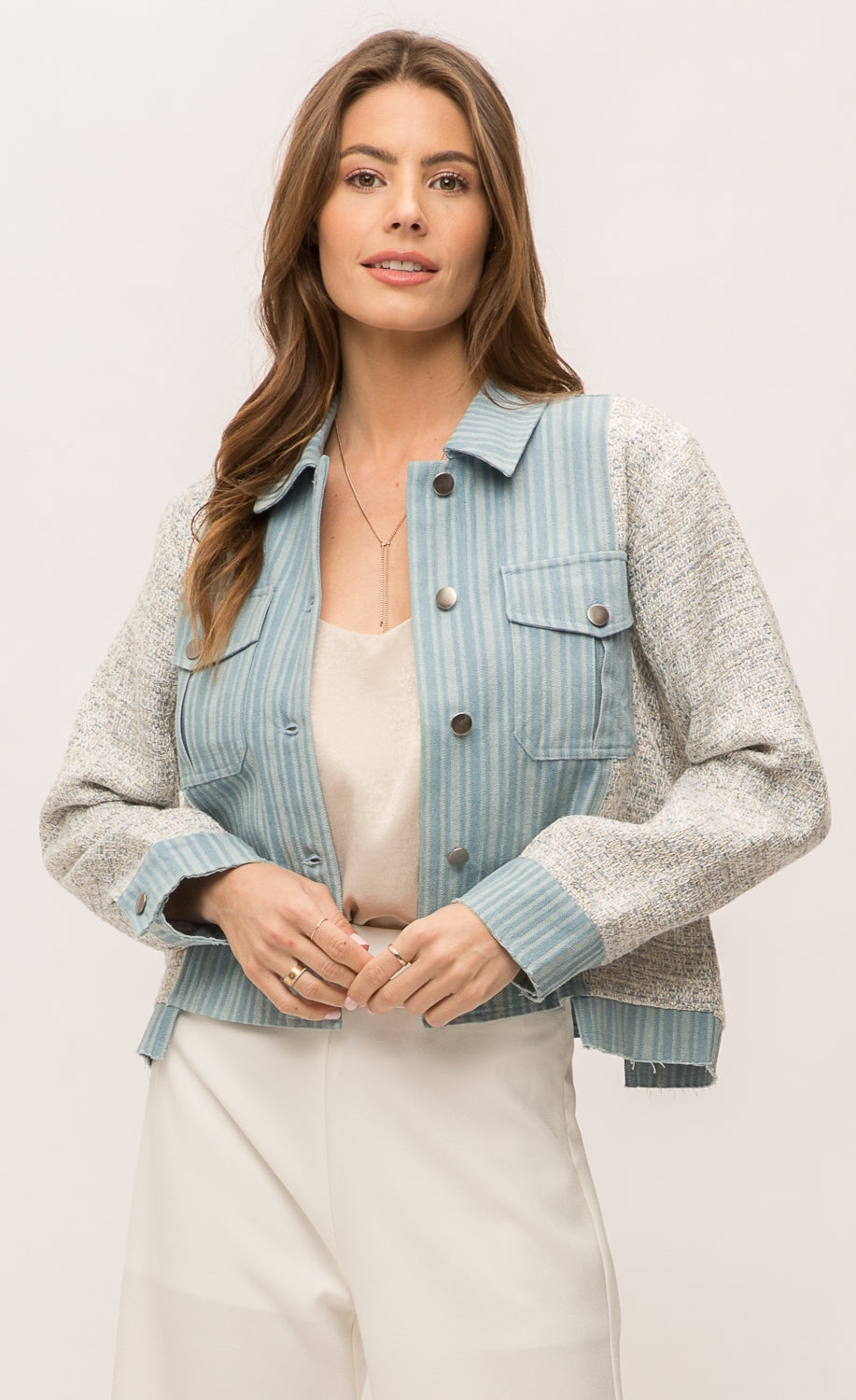 Front top half view of a woman wearing the Mystree Mix Media Jean Jacket with an off-white pant and over an off-white tank. This jacket has a striped denim body with woven grey and blue sleeves and sides. The front has two patch breast pockets and a button up front.